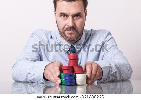 Mature man with poker chips on glass table, placing his bet - stock photo