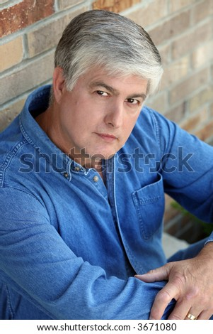 mature man with silver gray hair looking into camera