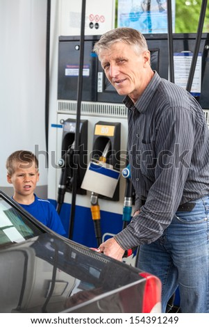 Mature man with son refueling vehicle with gasoline - stock photo