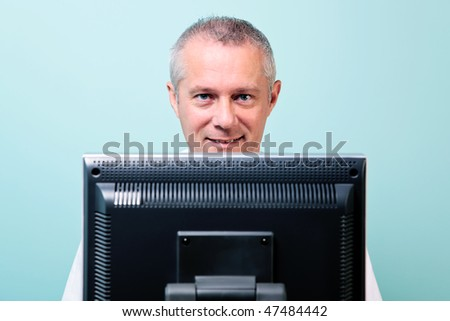 Mature man working at a computer looking over the screen - stock photo