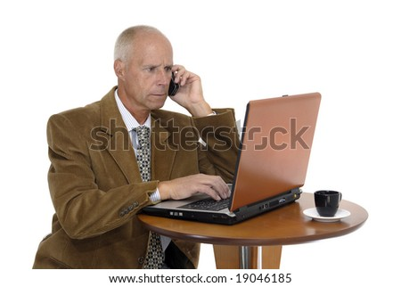Mature man working in is laptop  with a cellphone isolated in white