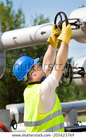 Mature man working on valves on pipes on oil plant - stock photo
