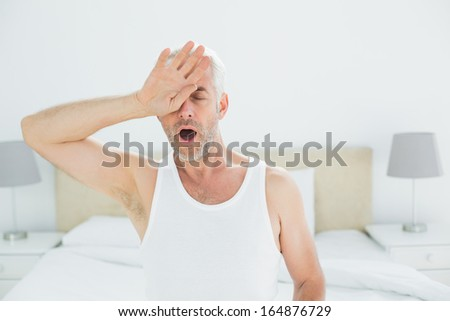 Mature man yawning while sitting in bed at home
