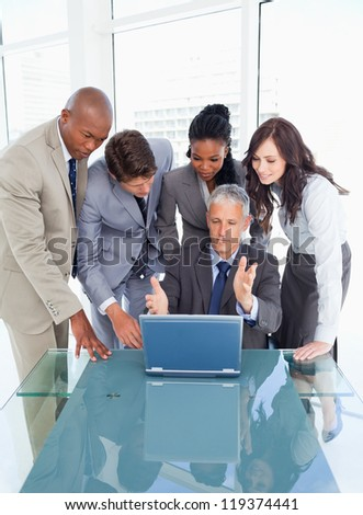 Mature manager earnestly giving explanations to his team with a laptop
