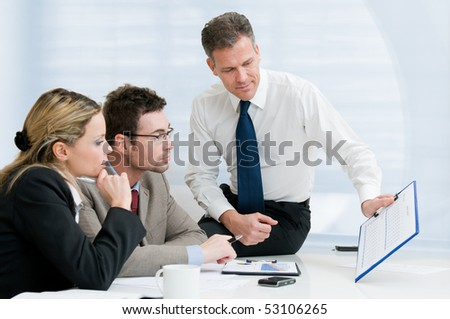 Mature manager giving a presentation to his business colleagues in modern office - stock photo