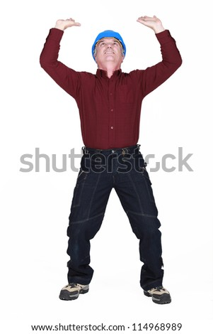 mature manual worker lifting weight - stock photo
