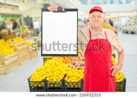Mature market vendor holding a clipboard in front of an aisle with fruits and vegetables - stock photo
