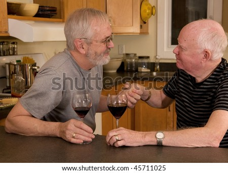 Mature married gay couple having wine and showing affection - stock photo