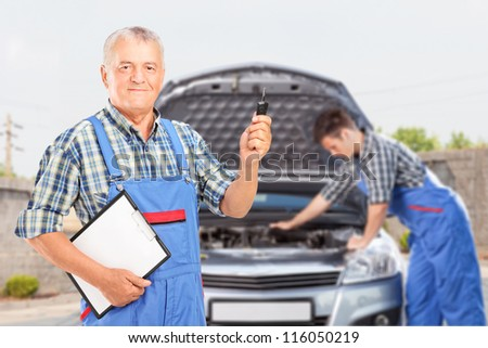 Mature mechanic in uniform holding a car key and another mechanic performing a car check in the background - stock photo