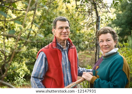 Mature, middle-age or senior couple standing at their garden gate - stock photo