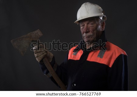 Mature miner covered in coal dust holding an axe