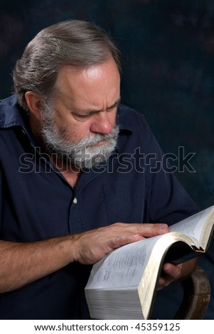 Mature minister with gray beard studies his bible. - stock photo