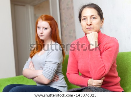 Mature mother and daughter after quarrel at home. Focus on parent - stock photo