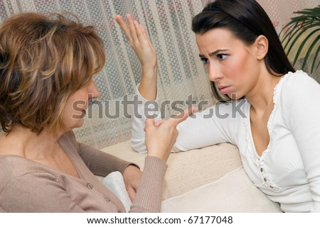 Mature mother and her daughter sitting on the sofa and serious talking. - stock photo