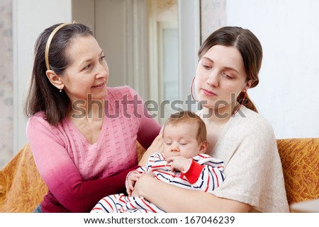 Mature mother asks for forgiveness from adult daughter with baby after quarrel at home - stock photo