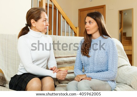 Mature mother with  teen daughter having serious talking in home