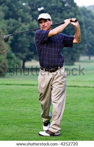 Mature nicely dressed man finishes swing after hitting golf ball with driver. - stock photo
