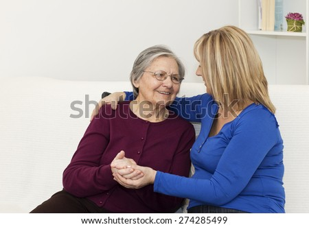 Mature nurse  holding hand her senior woman patient while they sitting on the sofa in the living room. - stock photo