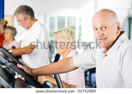 Mature older man exercising in the gym - stock photo
