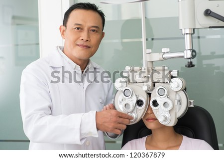 Mature optician demonstrating eye checkup with female patient - stock photo