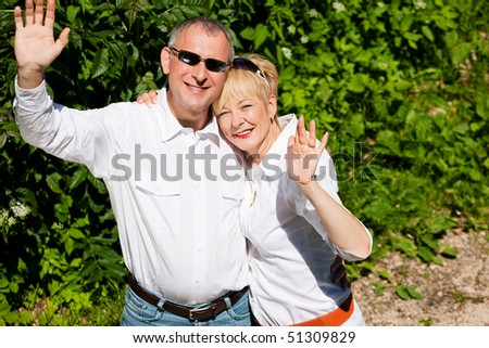 Mature or senior couple at a summer day waving their hands at the viewer - stock photo