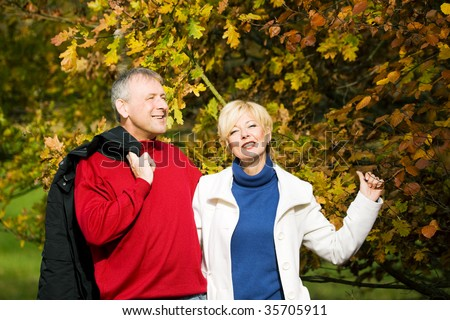 Mature or senior couple deeply in love having a walk holding each other tight in a autumn scenery with yellow leaves - stock photo