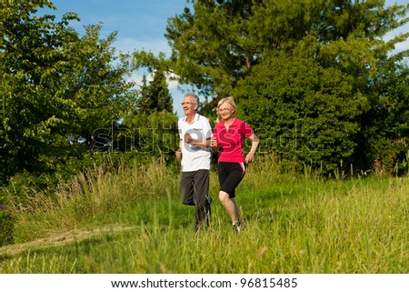 Mature or senior couple doing sport outdoors, jogging down a path in summer - stock photo