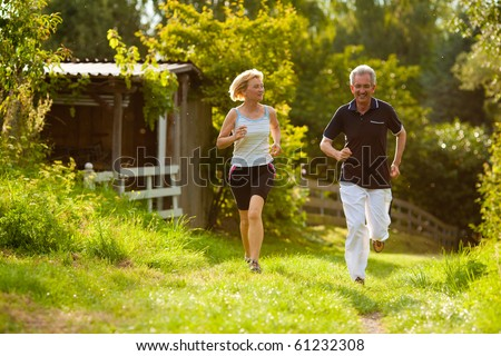 Mature or senior couple doing sport outdoors, jogging down a path in summer, the sun is low on evening - stock photo