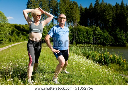 Mature or senior couple in jogging gear doing sport and physical exercise outdoors, stretching and gymnastics