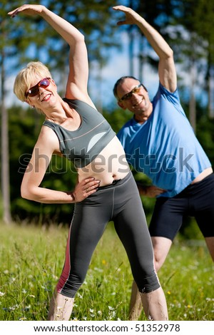 Mature or senior couple in jogging gear doing sport and physical exercise outdoors, stretching and gymnastics - stock photo