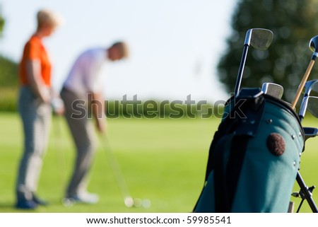 Mature or senior couple playing golf, FOCUS IS ON BAG IN FRONT - stock photo