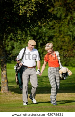 Mature or senior couple playing golf, walking down the course - stock photo