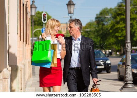 Mature or senior couple strolling through the city with shopping bags in spring on a sunny day