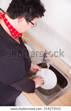 Mature overweight woman washing dishes in the kitchen. - stock photo