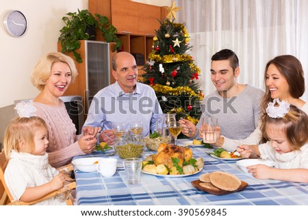 Mature parents with adult kids and grandchildren celebrating New Year today