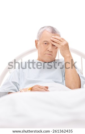 Mature patient having a headache and lying in a hospital bed isolated on white background - stock photo