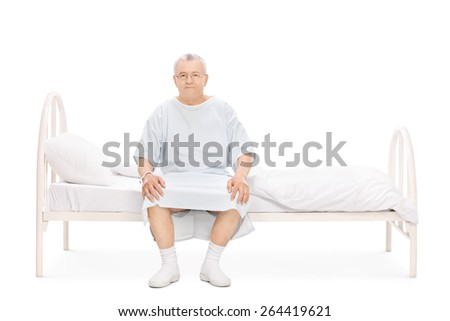 Mature patient in a hospital gown sitting on a bed and looking at the camera isolated on white background - stock photo