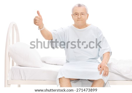 Mature patient sitting on a hospital bed, giving a thumb up and looking at the camera isolated on white background - stock photo
