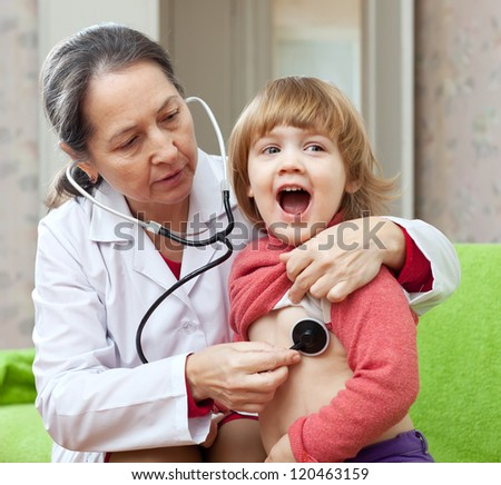 mature pediatrician doctor examining baby with  stethoscope. Focus on woman - stock photo