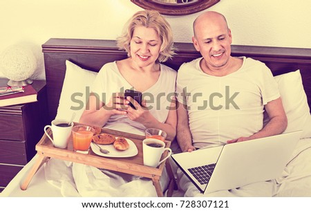 Mature positive couple reading news from notebook as having breakfast