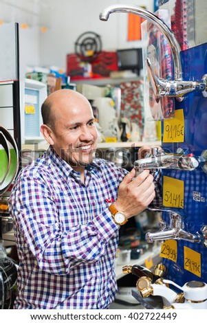 Mature positive man selecting heating water tap in household store