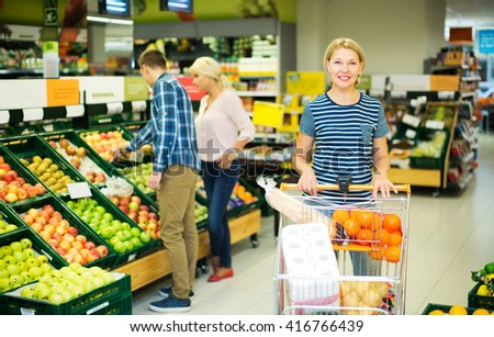 Mature positive woman choosing seasonal fruits in grocery section of supermarket