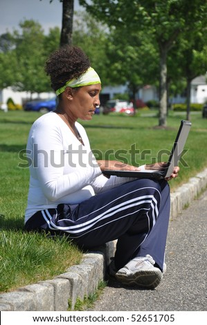 Mature Pregnant Latin Woman on Computer Surfing the Internet for prenatal care - stock photo