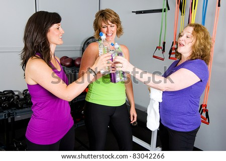 mature, pretty, women drinking water after a workout at a gym. - stock photo