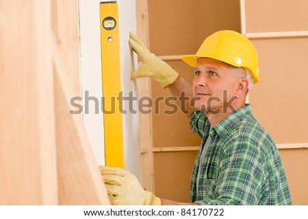 Mature professional handyman with spirit level working on home renovations - stock photo