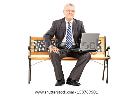 Mature professional man sitting on a wooden bench and working on a laptop isolated on white background - stock photo