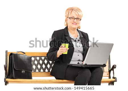 Mature professional woman with coffee cup working on a laptop and sitting on a bench isolated on white background - stock photo