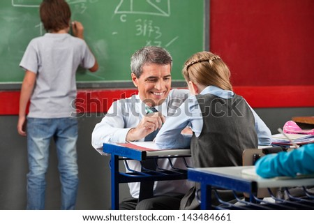 Mature professor assisting little schoolgirl at desk in classroom - stock photo