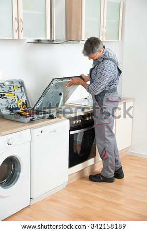 Mature repairman examining stove in the kitchen