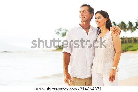 Mature Retired Couple Enjoying Sunset on Beach Vacation - stock photo